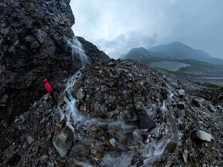 man in red stands under a waterfall on a black rock in the mountains on a cloudy rainy day Фото со стока - 119066587
