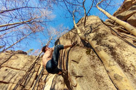 rock climber climbs a boulder over a rock without insurance Фото со стока