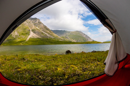 View from inside the tent out of the mountains and lake in the summer Фото со стока - 119771708