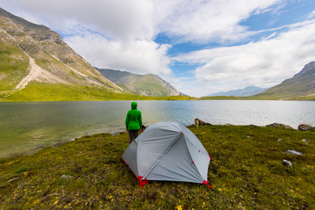 Gray tent stands in a meadow in the mountains near the lake in a thunderstorm Фото со стока