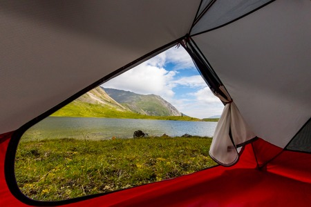 View from inside the tent out of the mountains and lake in the summer Фото со стока - 119771721