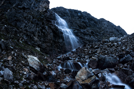Large mountain waterfall in the mountains on the dark wet rocks, evening landscape long exposure Фото со стока - 119771793