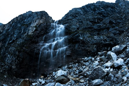 Large mountain waterfall in the mountains on the dark wet rocks, evening landscape long exposure Фото со стока - 119771798