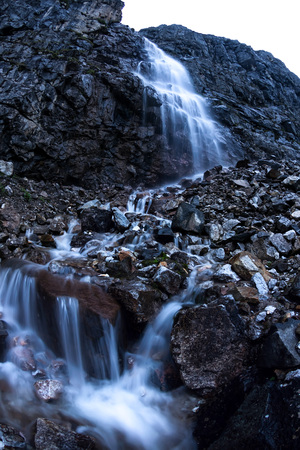 Large mountain waterfall in the mountains on the dark wet rocks, evening landscape long exposure
