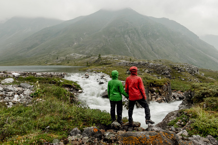 Couple of tourists standing by the mountain river on a foggy summer day in the rain Фото со стока - 119771826