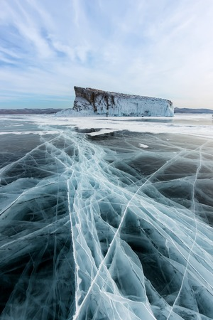 line cracks of Lake Baikal ice from Olkhon in the winter with cirrus clouds Фото со стока