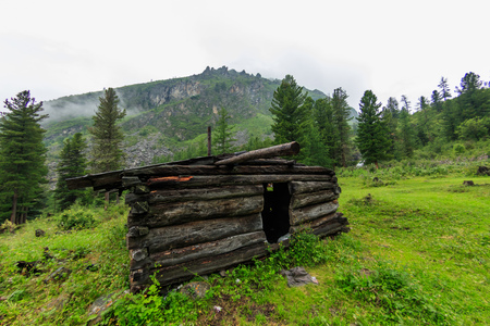 Old abandoned wooden house stands in the summer in the mountains of cloud