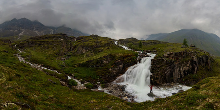 man in red stands under waterfall on black rock in mountains on cloudy rainy day.. Wide panorama Фото со стока - 119848824
