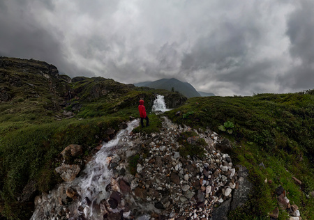 man in red stands under waterfall on black rock in mountains on cloudy rainy day.. Wide panorama Фото со стока - 119848837