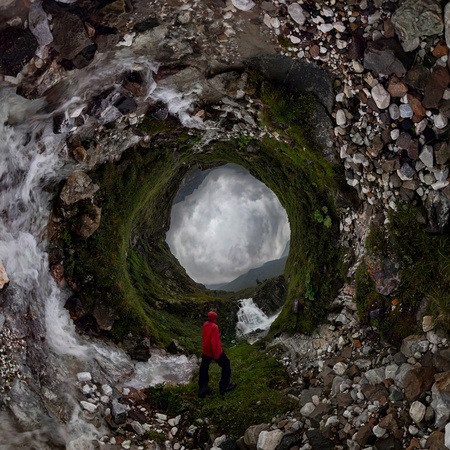 man in red stands under waterfall on black rock in mountains on cloudy rainy day.. . Tiny little planet 360 Фото со стока