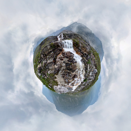 Mountain waterfall stream in misty rainy weather in the valley. Tiny little planet 360 Фото со стока