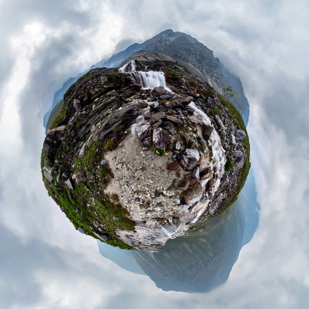 Mountain waterfall stream in misty rainy weather in the valley. Tiny little planet 360 Foto de archivo