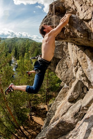 Climber Extreme climbs a rock on a rope with the top insurance, overlooking the forest