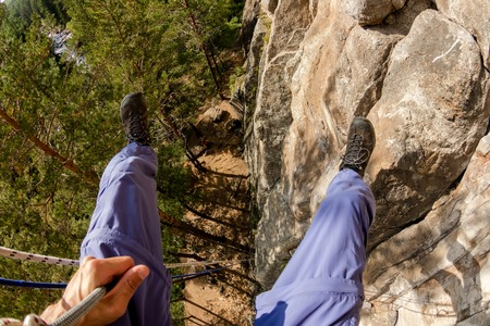 Climbers legs hanging on a rope in a harness, first person view from top to bottom Фото со стока