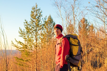 man backpacker stands in forest at sunset in fall in yellow trees