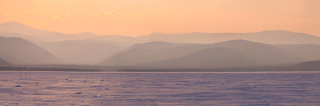 Wide angle panorama winter mountain,misty hills mountain tops in pink dawn