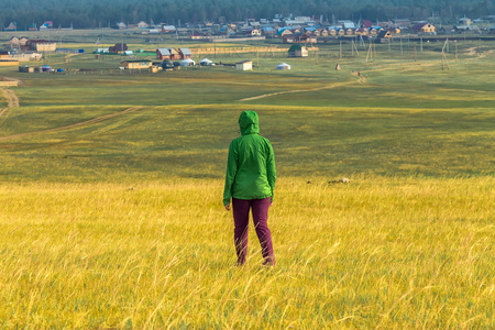 tourist girl walks in the yellow grass on the field overlooking the village and mountains Фото со стока