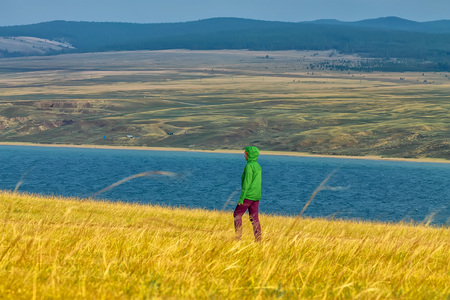 tourist girl walks in yellow grass across a field overlooking the water and mountains