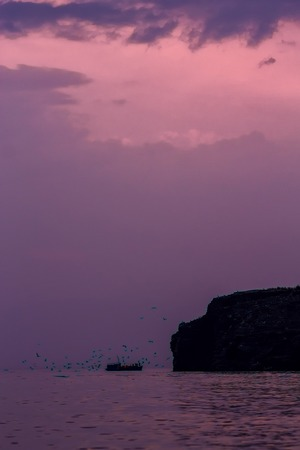 ship sails on a background of purple sunset sky on the waves of Lake Baikal from Olkhon