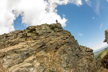 man hike on the peak of rocks mountain on blue sky and clouds background Фото со стока