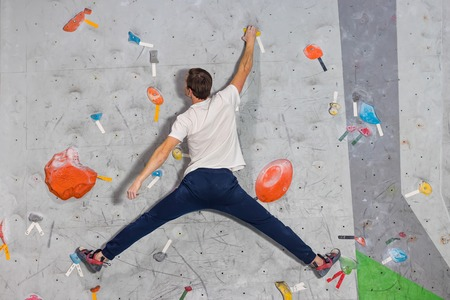 Climber man hanging in a twine on a climbing wall bouldering the wall, inside on colored hooks