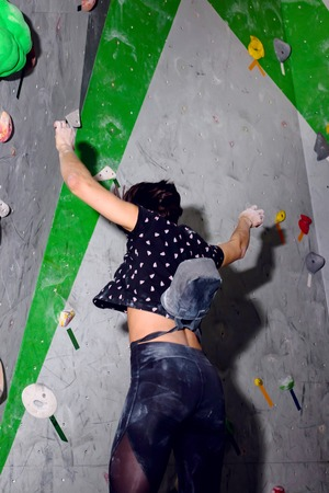 rock climber woman falls off the wall in the boulder hall Фото со стока