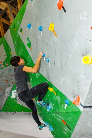 Rock climber woman hanging on a bouldering climbing wall, inside on colored hooks Imagens