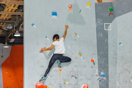 Kletterer-Frau hängt an einer Boulder-Kletterwand, innen an farbigen Haken Standard-Bild