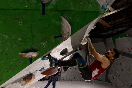 Rock climber man hanging on a bouldering climbing wall, inside on colored hooks Imagens