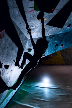dark silhouette of a rock climber woman climbing in a boulder hall on the wall