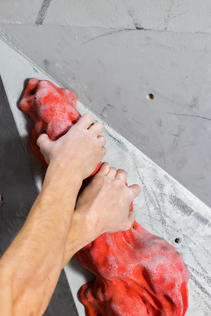 two white mans hands are held on the oval passive hook of the climbing wall