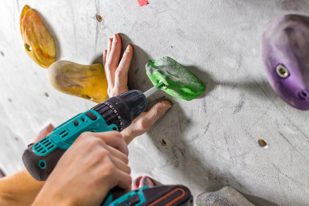 Rock climber fastens the hook with a screwdriver at the climbing wall in the boulder hall