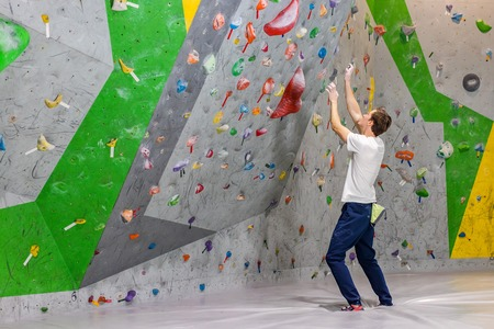 climber explores and develops a route on a climbing wall in the boulder hall Фото со стока