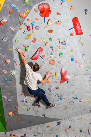 Rock climber man hanging on a bouldering climbing wall, inside on colored hooks Фото со стока