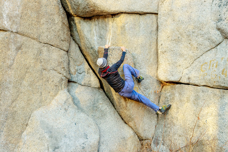 rock climber climbs a boulder over a rock without insurance Banco de Imagens - 126054046