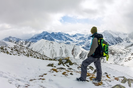 backpacker man high in snowy mountains. Portrait of a mountaineer on a background of mountains