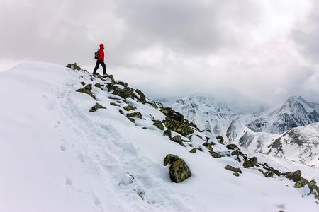 backpacker man high in snowy mountains. Portrait in a red jacket 版權商用圖片