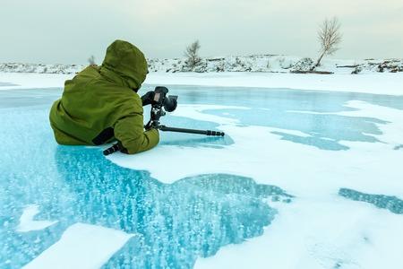 Fotograf macht Bilder von Methangasblasen, die in klares Eis eingefroren sind Baikalsee, Russland