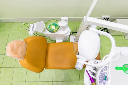 Medical interior, dental office with an orange chair, lamp and equipment. stomatology concept top view Фото со стока