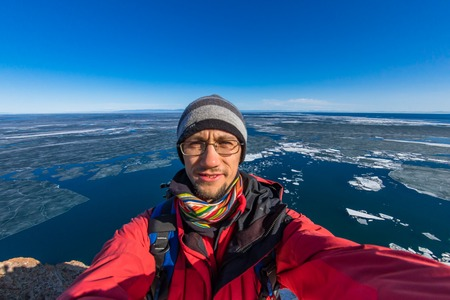 selfie portrait of a man in a red jacket on the spring lake Baikal