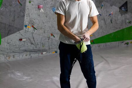 Rock climber man shoved his hands into a bag of magnesia powder behind his back in the boulder hall Фото со стока