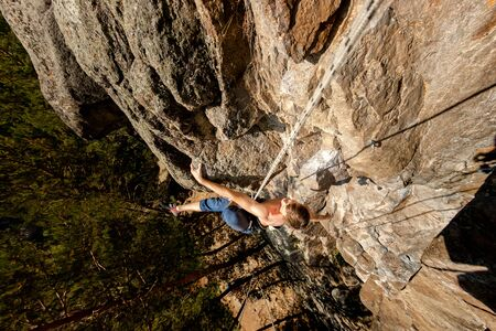 Climber Extreme climbs a rock on a rope with the top insurance, top view from above Фото со стока - 126055668