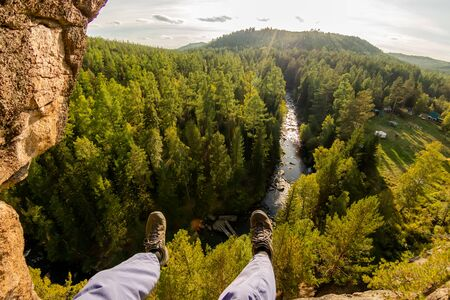 Climbers legs hanging on a rope in a harness, first person view to river in forest