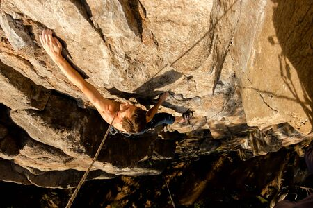 Climber Extreme climbs a rock on a rope with the top insurance, top view from above Фото со стока