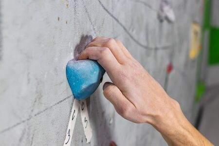 white mans hand is holding on the climbing wall Фото со стока - 126055809