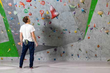 Rock climber stands and looks at the climbing wall with hooks in the boulder hall Фото со стока - 126055823