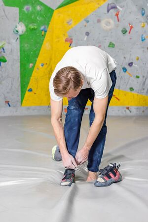 Rock climber puts on rocky shoes in a bouldering hall at a climbing gym.