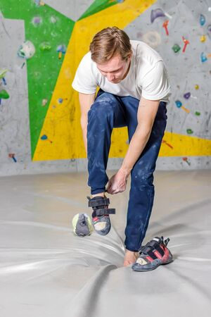Rock climber puts on rocky shoes in a bouldering hall at a climbing gym. Фото со стока