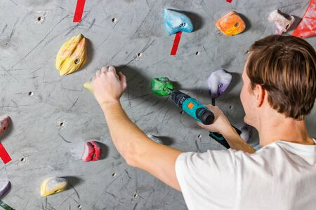 Rock climber fastens the hook with a screwdriver at the climbing wall in the boulder hall.