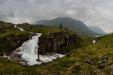 man in red stands under waterfall on black rock in mountains on cloudy rainy day.. Wide panorama Фото со стока